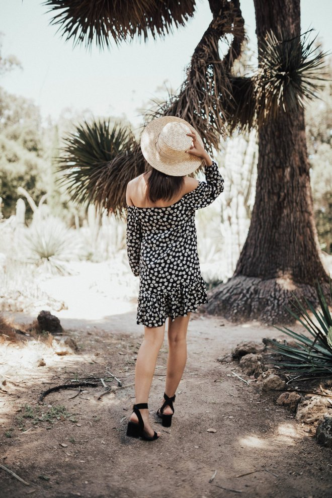 Girl in dress and straw hat among joshua trees