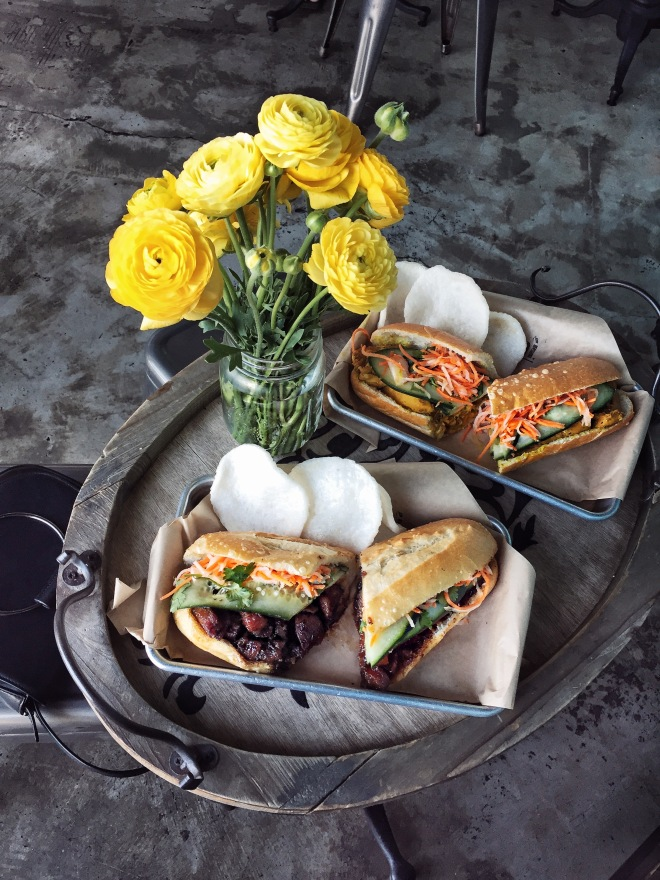 Yellow Flowers beside banh mi sandwiches